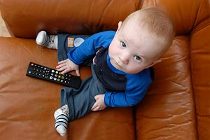 Little baby boy playing with TV remote